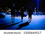 Three silhouettes walking in a...
