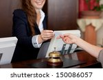Stock photo smiling female receptionist passing card to guest 150086057