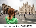 Young woman taking picture of Duomo di Milano (Milan Cathedral), Milan, Italy, motion blurred people on square - stock photo