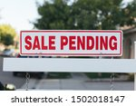 Small photo of Sale Pending real estate sign by a newly listed house.