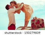 Happy honeymoon (vacation) concept. Young married couple of hipsters in trendy clothes standing on a boat, hugging and kissing. Sunny summer day, blue sky. Outdoor shot - stock photo