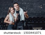 Small photo of Young sporty couple guy and girl standing in gym. During this, the white scumbag is held on the neck. Standing on a black background and looking away.