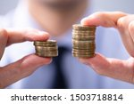 Man Holding Two Coin Stacks To...