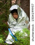 Small photo of person wrapped in a tinfoil blanket looks scared, cold and lost in the woods