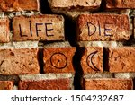 Small photo of words - life and die on the background of broken brick wall divided by cracks. astrology sign of moon and sun