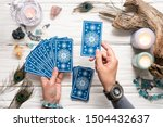 Small photo of Fortune teller woman and a blue tarot cards over white wooden table background.