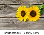 Two Sunflowers On Wooden Table...