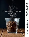 Coffee beans in a transparent glass on a wooden surface with a wording of International Coffee Day - stock photo