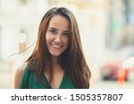 Small photo of Young pretty likable cheerful woman posing summer city outdoor. Beautiful self-confident girl dressed in emerald-colored jumpsuit with long brown hair walking street enjoing her life, urban lifestyle