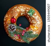 Small photo of Christmas cake with nuts - Bolo Rei is a traditional Xmas cake with fruits, raisins, nut and icing on black background. Top view. Copy space