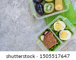 Two lunch boxes with sandwich and egg. Dsert-fruit. Top view.