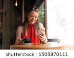 Stock photo cheerful young woman using mobile phone on coffee break in cafe online messaging cafeteria 1505870111