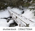 A Snow Covered Bridge Over A...