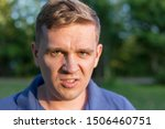 Small photo of Enraged infuriated man baring his teeth. Portrait of a young man on nature background. Emotion facial expression.