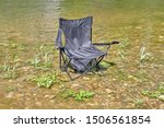 Small photo of A broken and torn tourist chair stands in the water. Tourist litter, environmental destruction, nature destruction