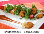 Popcorn shrimp and baby arugula salad with grape tomatoes and white sweet onions.  - stock photo