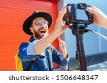 Small photo of social media influencer personality creating content. man shooting video of himself using camera on tripod. Smiling bearded hipster singer communicating with subscribers outdoor interview concept.