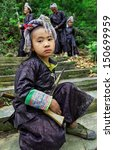 Small photo of GUIZHOU, CHINA - APRIL 10: Unidentified Chinese boy at the age of 8 years old, in traditional ethnic clothing of Miao tribe, holding an old musket, April 10, 2010. Basha Village, Congjiang County.