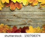 Small photo of autumn background with colored leaves on wooden board