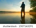 Angler catching the fish in the lake during sunrise