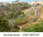 Extreme narrow winding route along a Barranco above the city of Los Realejos in the north of the Canary Island of Tenerife overlooking the colorful houses of the city below.
