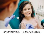 Small photo of Lovely little kid smiling while talking with the pediatric dentist after doing a tenth examination in a pediatric stomatology.