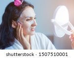 Beautiful woman looks at mirror during charming beautiful woman mask her face by using collagen mask sheet for moisturizing and nourishing facial skin, anti wrinkle, time defiance in the morning.