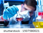 Small photo of Tubes with colored chemical liquids in the laboratory. Research in the field of pharmacology. The scientist checks the hypothesis. Chemical experiments.