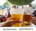 Couple Holding Beer Glasses In...