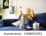 Small photo of Mischievous preschooler boy play the music using kitchen tools and utensils. Funny drum part from little boy. Funny and developmental activity for creative kids at home