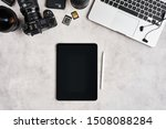 ZAGREB, CROATIA - SEPTEMBER 10, 2019: Top view on workplace of photographer or graphic designer. Apple iPad Pro, iPhone, MacBook Pro, Nikon Z6 mirrorless camera and lenses on grey concrete background. - stock photo