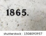 The year 1865 carved in stone and painted in black – a detail of an inscription produced that year
