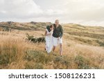 Small photo of Young couple man and woman in love walking on the field on the mountain in autumn or summer day hugging together having fun bonding flirting flirt husband and wife lovers