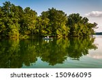 trees and boat reflecting in... | Shutterstock . vector #150966095