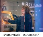 Small photo of Moscow, Russia - September 14, 2019: Advertising reflections of Sephora store in glass of shopping center window. Woman makes payment for mobile phone on self-service checkout counter Beeline
