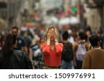 Sad depressed woman covers his eyes with his hands surrounded by people walking in crowded street. Panic attack in public place.
