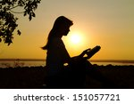 Silhouette Of A Girl Reading A...
