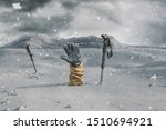 Small photo of Hiker stretching out his snow covered hand next to trekking poles to signal help because of snow avalanche . Danger extreme concept
