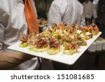 a waiter serving appetizers during a catered event - stock photo