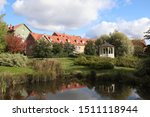 A view to the residential colorful houses over a small pond and a park. These modern houses are built on a traditional way. Scandinavian architecture. The photo is taken in Vantaa, Finland.