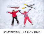 Skier and snowboarder are lying on snow with ski and snowboard and having fun. Aerial photo - stock photo