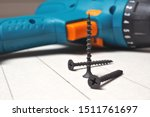 Screwdriver and screws lie on a sheet of drywall. The sheet is marked with a pencil. Close-up - stock photo