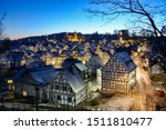 """Small photo of Freudenberg panorama in Sauerland Germany with historic black and white truss half timbered houses in the old town called """"Alter Flecken"""" at blue hour on a very cold evening in christmas time"""