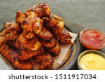 Fried chicken wings. Chicken wings on a dark background on a blackboard. Barbecue meat, grill. Sauce in bowls, ketchup, mayonnaise, mustard, cheese sauce. Appetizing fried meat. Place for your text