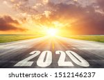Small photo of Road asphalt road with the inscription 2020 year with the rising sun in the morning. The concept of the beginning of new goals and affairs