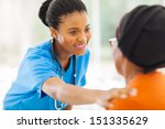 Small photo of caring african medical nurse comforting senior patient in office