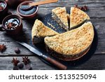 delicious Poppy Seed Crumble Cheesecake sliced on a black stone plate with cups of coffee on a rustic wooden table, horizontal view from above - stock photo