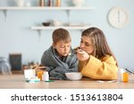 mother feeding her sick son... | Shutterstock . vector #1513613804