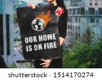 Stock photo the phrase our home is on fire and burning world icon drawn on a black carton banner in woman 1514170274