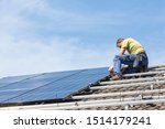 Installing solar photovoltaic panel system. Solar panel technician installing solar panels on roof. Alternative energy ecological concept. - stock photo